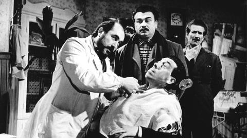 Mit Genuss beobachtet Peppone (Gino Cervi, Mitte), wie sich sein Lieblingsfeind Don Camillo (Fernandel, sitzend) versucht, sich dem Zahnarzt zu widersetzen.