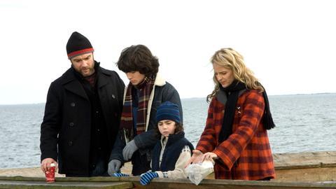Ned (Liev Schreiber, li.), Jeannie (Helen Hunt, re.) und die Kinder Jonah (Ezra Miller, 2.v.l.) und Ethan (Skyler Fortgang, 2.v.r.) verstreuen Ernies Asche im Meer.