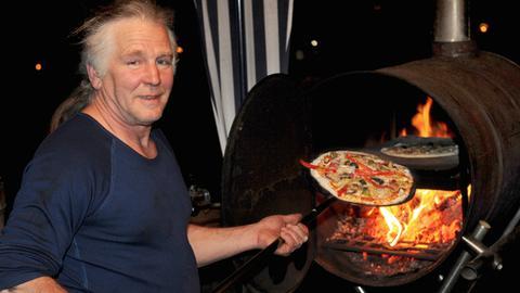 """Alex Eisert vor seinem Pizzaofen der """"dicken Emma""""."""
