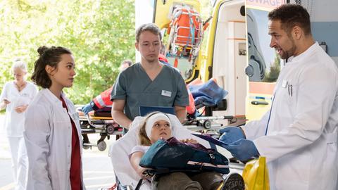 Nach einem Wanderunfall kommt Nadine Bütow (Tina Schorcht, M. mit Komparse) mit einem offenen Bruch ins Klinikum. Moreau (Mike Adler, r.) und Rebecca (Milena Straube, l.) übernehmen die Patientin.