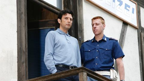 Kommissar Vincenzo (Enrico Ianniello, links) und Huber (Gianmarco Pozzoli, re.) haben den Hotelbesitzer Bini vorgeladen. Zwischen ihm und dem erschlagenen Senner hatte es seit längerem Streit gegeben.
