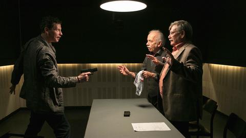 Während des Verhörs gelingt es dem Bankräuber Lutz Michel (Gerdy Zint, l.), Edwin (Tilo Prückner, 2.v.r.) und Günter (Wolfgang Winkler, r.), in der Wache als Geiseln zu nehmen.