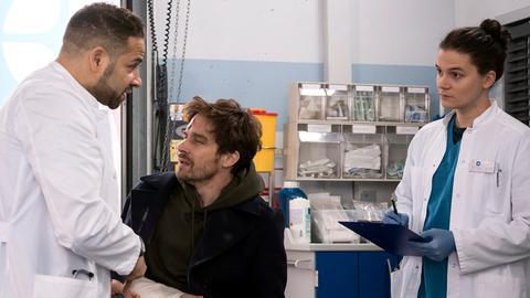 Matteo (Mike Adler, l.) ist wieder zurück am JTK und behandelt gemeinsam mit Tom (Tilman Pörzgen, r.) den Patienten Robert Müller (Nico Rogner, M.). Er hat nach einem Unfall mit einem Fahrradkurier Verletzungen am Auge, Arm und Finger.