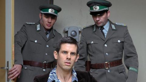 Robert Schnyder (Steffen Groth, M.) wird wegen Beihilfe zur Republikflucht inhaftiert und im Vernehmungsraum von Falk verhört.