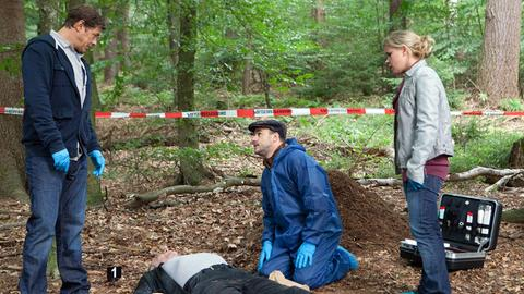 Finn Kiesewetter (Sven Martinek, l.), Pathologe Dr. Strahl (Christoph Tomanek, 2.v.r.) und Sandra Schwartenbeck (Marie-Luise Schramm, r.) mit der Leiche eines Mannes (Thomas Born) aus dem Hamburger Rotlichtmilieu, die auf einem Waldparkplatz gefunden wurde.