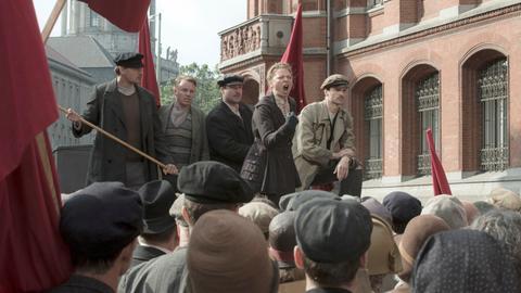 Dr. Völcker (Jördis Triebel, 2. v. re. oben) heizt die Masse bei den Mai-Unruhen an.