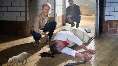 Kristina Katzer (Isabell Gerschke, l.) und Lukas Hundt (Oliver Franck, r.) entdecken Metzgermeister Lehmann tot auf dem Boden, getötet mit einem Bolzenschussgerät. Einziger Zeuge ist ein süßes Minischwein.