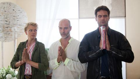 """Ommm: Kristina Katzer (Isabell Gerschke, l.) und Lukas Hundt (Oliver Franck, r.) ermitteln im Yogastudio von Rainer """"Ravi"""" Schaffrath (Simon Licht, M.)."""