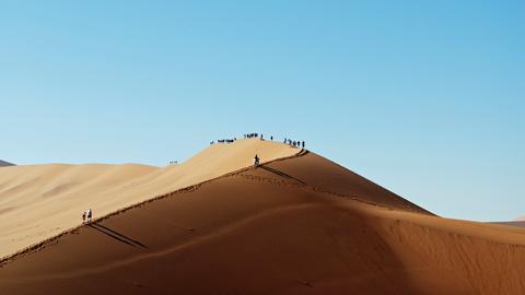 Die Reisenden erkunden die scheinbar endlose Wüste mit ihrer herrlichen Dünenlandschaft.