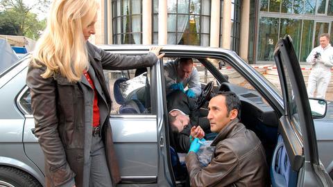 Kriminalrätin Susanne Meder (Marita Marschall) und ihr Kollege Cem Pamuk (Ercan Durmaz, vo. kniend) verschaffen sich am Tatort des ermordeten Christof Boll (André Willmund, im Auto liegend) einen ersten Überblick.