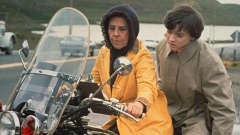 """Da ihr die Verkehrskontrolle zu lang dauert, """"leiht"""" sich Maude (Ruth Gordon, li.) kurzerhand das Polizeimotorrad aus und saust mit Harold (Bud Cort, re.) davon."""