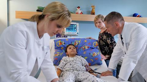 Fritz Kamp (Lucano Resta, mi.) kann seine Beine nicht mehr spüren. Seine Mutter Friederike Kamp (Sophie Rogall, 2.v.re.) macht Fritz' Vater für den Unfall verantwortlich und die Komplikationen steigern ihre Wut noch. Als sie dies jedoch anfängt an Dr. Peters (Anja Nejarri, li.), Dr. Kaminski (Udo Schenk, re.) und sogar an ihrem Sohn auszulassen, bittet Dr. Kaminski sie zu seinem Gespräch.