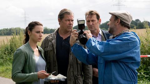 Strahl (Christoph Tomanek, r.) zeigt Nina (Julia Schäfle, l.), Finn (Sven Martinek, 2.v.l.) und Lars (Ingo Naujoks, 2.v.r.) was ihm am Auto der Toten aufgefallen ist.