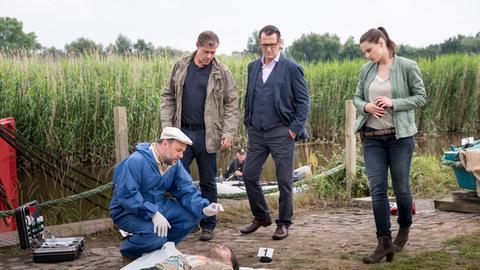 Strahl (Christoph Tomanek, l.) erklärt Finn (Sven Martinek, 2.v.l.), Lars (Ingo Naujoks, 2.v.r.) und Nina (Julia Schäfle, r.), dass das Opfer vermutlich durch einen Fußtritt von einem Boot gestoßen wurde.
