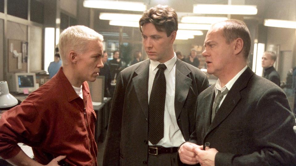 Kommissar Beck (Peter Haber, re.) erklärt seinen Mitarbeiteren Benny Skacke (Figge Norling, li.) und Gunvald Larsson (Mikael Persbrandt), dass sie in einem Fall von Internet Pornografie ermitteln.