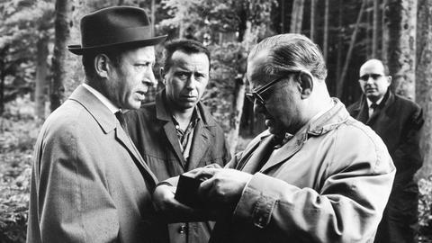 Waldarbeiter haben beim nahe gelegenen Rabenkopf eine Leiche entdeckt. Kommissar Freytag (Konrad Georg, links) und Polizeihauptmeister Peters (Willy Krüger, 2.v.r.) ermitteln.