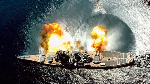 Vogelperspektive auf das Kriegsschiff USS IOWA, das während einer Übung in den Gewässern vor Vieques alle seine 15 Kanonen abfeuert.