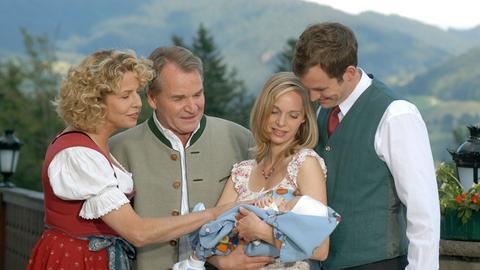 Richard Steiner (Fritz Wepper, 2.v.li.) und seine Gattin Christina (Michaela May, li.) bewundern das Baby von Toni (Stefan Murr) und Susi (Jenny-Marie Muck).