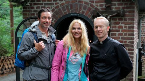 Moderator Marco Schreyl (l) wandert mit Sonya Kraus, Schauspielerin und Autorin, im Birgeler Urwald am Niederrhein. Am Birgeler Pützchen treffen Sie Pfarrer Wieners (r).