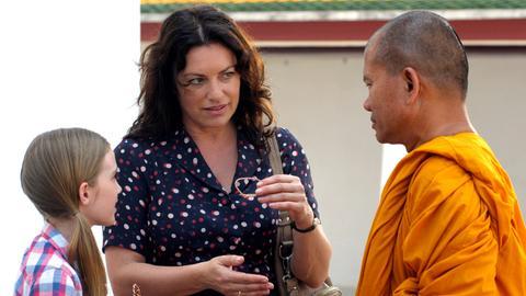Sabine (Christine Neubauer) und ihre Tochter Emma (Hanna Heile) lassen sich von einem Mönch buddhistische Traditionen erläutern.