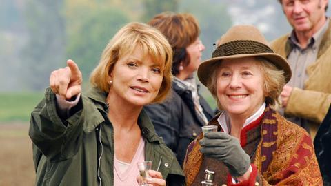 Barbara (Uschi Glas, li.) und ihre Mutter Elisabeth (Bibiana Zeller) genehmigen sich ein Schlückchen und vergessen dabei, dass sie eingeladen sind.
