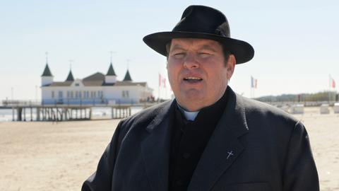 Pfarrer Braun (Ottfried Fischer) macht in seiner neuen Pfarrei auf Usedom einen Strandspaziergang.