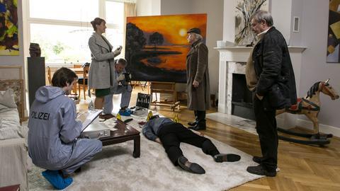 Patrick Wilke liegt erschlagen in seinem Wohnzimmer, Dr. Rosalind Schmidt (Helene Grass, l.) und Edwin (Tilo Prückner, 2.v.r.) flirten vor dem Toten. Günter (Wolfgang Winkler, r.) kann es nicht glauben.
