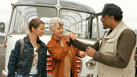 Marianne (Nicole Heesters, Mitte) und ihre Enkeltochter Nellie (Vanessa Berthold) haben dem Reiseveranstalter Calvin Baker (Ron Williams) aus der Patsche geholfen.