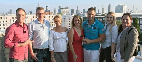 Drei Paare aus drei Städten konkurrieren darum, wer der beste Gastgeber in Hessen ist: Moderator Mathias Münch mit Markus Stiehl und Ingrid Gehre aus Laubach, Sabine und Armin Lerch aus Bad Soden-Salmünster sowie Saskia und Anette Hahn aus Weilburg.
