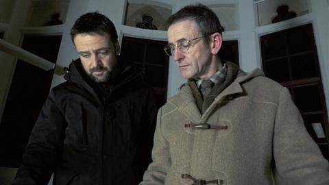 Chief Inspector Tom Mathias (Richard Harrington, li.) lässt sich von dem Gilde-Mitarbeiter Joseph Roberts (Llion Williams) Unterlagen zeigen, die ihm Hinweise in einem Mordfall geben könnten.