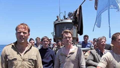 Der Brite Billy Hardacre (Lenny Wood, 4.v.li.) entdeckt gemeinsam mit Declan McDermott (Ciaran McMenamin, Mitte) und Coutts (Nicholas Burns, li.), dass ein amerikanischer Bomber sich dem U-Boot nähert.