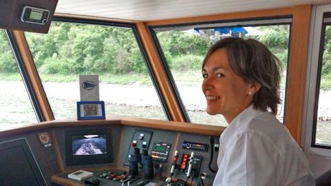 Die Kapitänin Bianca Rössler-Kullmann am Steuer eines ihrer Fahrgastschiffe auf dem Rhein.