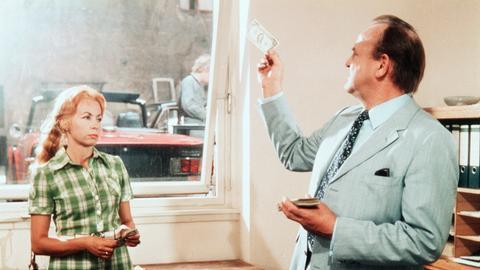 Bei seinen Nachforschungen stößt Frank Kross (Siegfried Wischnewski) auf falsche Dollars; links im Bild Dolly Velbinger-Ebert als Frau Laumen.