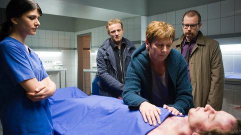 Vier Person stehen um eine obduzierte Leiche