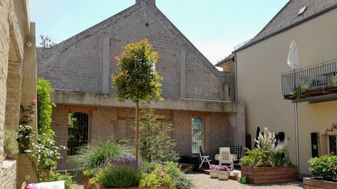 """Wohnen in einem ehemaligen Weinbaubetrieb: der Innenhof des """"Kapellenhofes"""" in Geisenheim. Die denkmalgeschützte Fassade eines Wirtschaftsgebäudes musste stehen bleiben."""