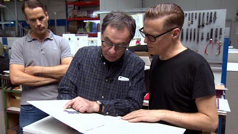 Gerhard Steidl (Mitte) bespricht mit Rocksänger und Fotograf Bryan Adams den Einband für dessen neues Fotobuch.