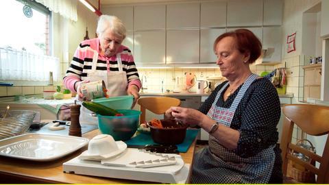 Frau Schubert mit ihrer Freundin bei Küchenarbeit.