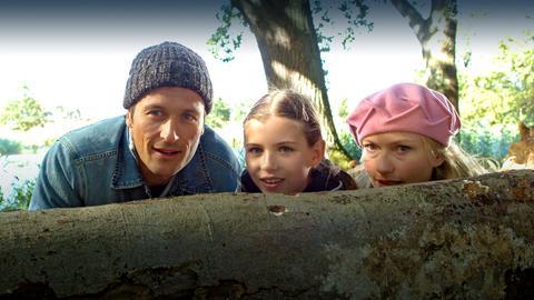 Thomas (Markus Knüfken), Gabriela (Johanna Christine Gehlen, li.) und Edda (Petra Kelling) schauen über einen Baumstamm.