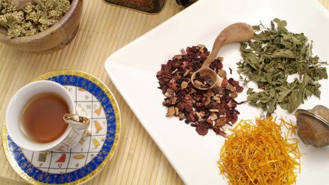 Lose Schafgarbe-, Ringelblumen-, Brennessel- und Früchteteemischung auf einem Teller mit Teesieb und einer vollen Tasse Tee.