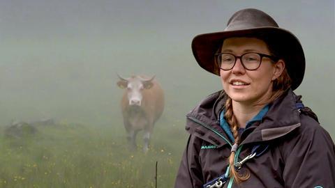 Ein junges Mädchen schmunzelt. Im Hintergrund ist eine Kuh im Nebel auf der Weide zu sehen.
