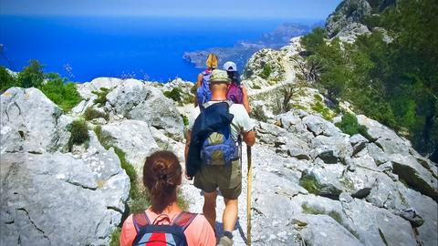 Vier Wanderer im Gebirge von Mallorca mit Blick aufs Meer.