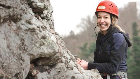 Christina steht strahlend, gesichert und mit Helm, vor einem Felsen und ist bereit loszuklettern.