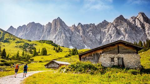 Zwei Wanderer laufen an einer Hütte vorbei mit Blick auf die Karwendel-Gebirgsgruppe.