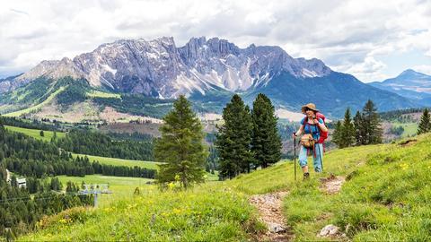 Wandererin auf dem Berg mit Gebirge im Hintergrund.