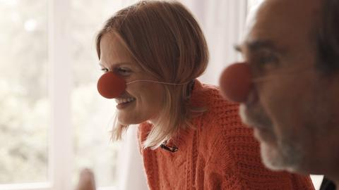 Anne-Katrin Eutin sitzt mit Clownsnase und einem weiteren Clown vor einem Laptop und lacht.