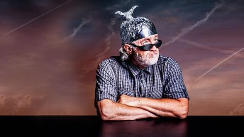 Ein alter Mann trägt einen gebastelten Aluhut auf dem Kopf und Sonnenbrille im Gesicht und schaut bockig und mit verschränkten Armen aus dem Bild heraus.
