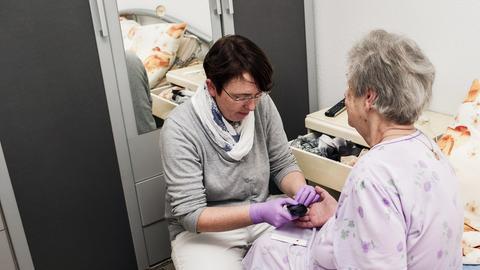 Eine Mitarbeiterin eines ambulanten Pflegedienstes misst einer Patientin den Blutzuckerwert.