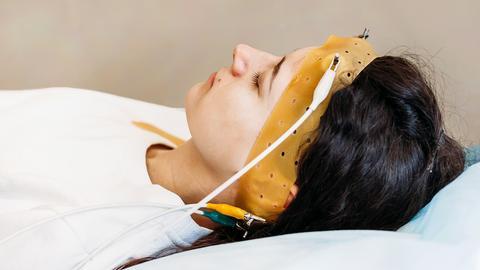 Eine Frau liegt im Schlaflabor mit Elektroden an der Stirn