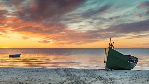 Ruderboot am Strand bei Sonnenuntergang.