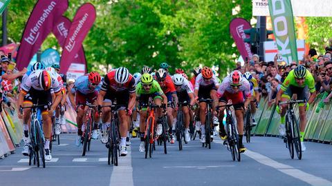 """Radrennfahrer in Aktion beim Radrennen Eschborn – Frankfurt. Im Hintergrund sind einige Fahnen mit dem """"hr fernseheh""""-Logo zu sehen."""
